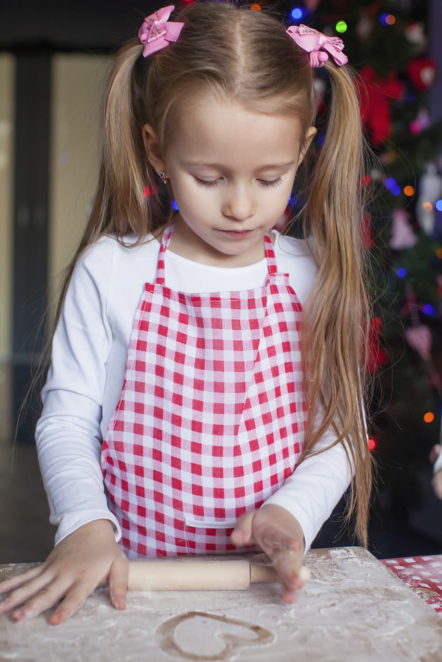 Little happy girl with rolling pin baking gingerbread cookies for Christmas